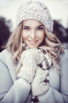 Portrait of smiling woman wearing woolly hat and gloves - GDF01187