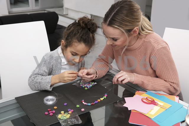 Mother and little daughter stringing beads for creating a necklace - GDF01190