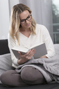 Smiling woman reading book on the couch - GDF01193