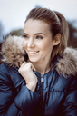 Portrait of smiling woman wearing winter jacket with fur collar - GDF01196