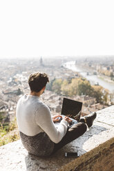 Italy, Verona, tourist using laptop, observation point - GIOF03579