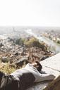 Italy, Verona, tourist lying on balustrade - GIOF03585