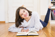 Portrait of happy girl lying on the floor with book - LVF06498
