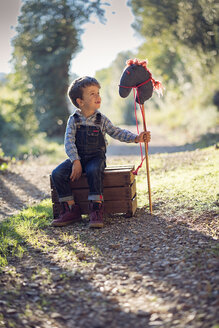 Boy with a hobby horse sitting on wooden box - XCF00162