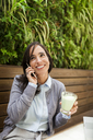 Smiling woman on cell phone in garden cafe - VABF01391