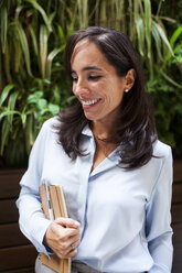 Smiling businesswoman holding notebook in garden cafe - VABF01397