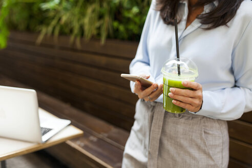 Businesswoman holding smoothie using cell phone in garden cafe - VABF01400