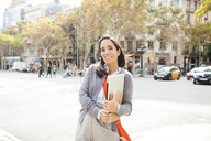 Portrait of smiling woman holding notebook in the city - VABF01403