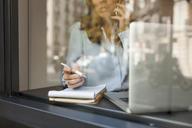 Busy businesswoman working behind window pane - VABF01409