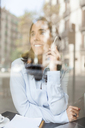Smiling businesswoman on cell phone behind window pane - VABF01412