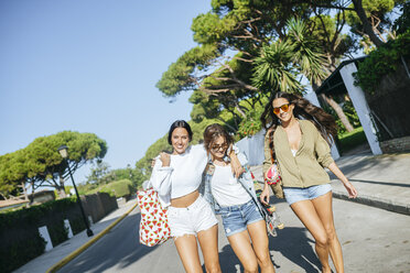 Three smiling young women walking on the street - KIJF01735