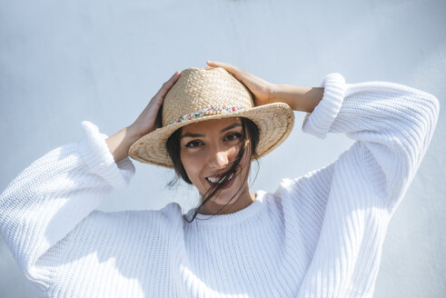Portrait of laughing young woman wearing straw hat - KIJF01738