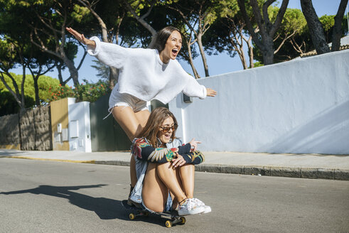 Two laughing friends together on skateboard - KIJF01744