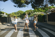 Three friends crossing pedestrian crossing showing victory sign - KIJF01750