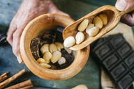Man's hands pouring almonds in a wooden bowl with chocolate - KIJF01777