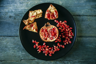 Half of pomegranate and pomegranate seed on black plate - KIJF01783
