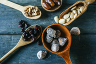 Wooden spoon of dried figs and nuts and other dried fruits in the background - KIJF01792