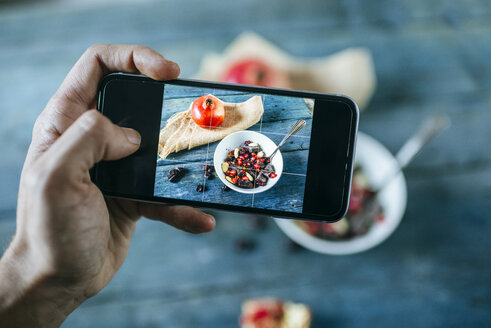 Man's hand taking a picture with smartphone of bowl with dessert of almonds, pomegranate and chocolate - KIJF01795