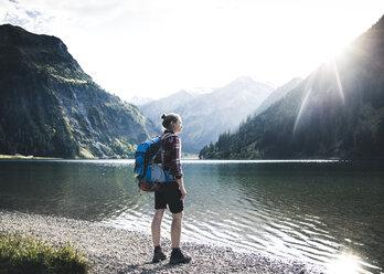 Austria, Tyrol, young woman hiking at mountain lake - UUF12469