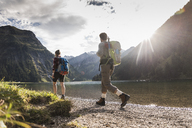 Austria, Tyrol, young couple hiking at mountain lake - UUF12472