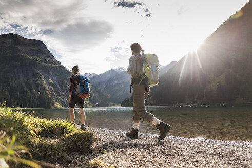 Austria, Tyrol, young couple hiking at mountain lake - UUF12472