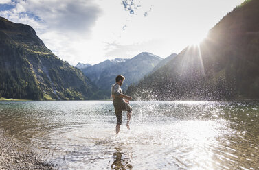 Austria, Tyrol, hiker splashing in mountain lake - UUF12478