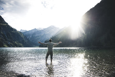 Austria, Tyrol, hiker standing with outstretched arms in mountain lake - UUF12481