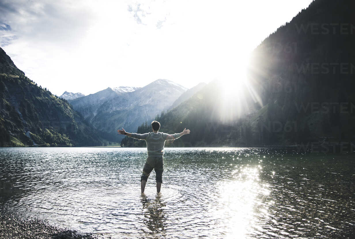 Austria, Tyrol, hiker standing with outstretched arms in mountain lake - UUF12481 - Uwe Umstätter/Westend61
