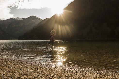 Austria, Tyrol, hiker in yoga pose refreshing in mountain lake - UUF12487