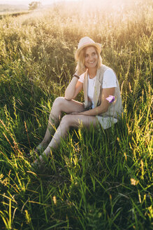 Blond woman sitting on meadow in summer - VPIF00267
