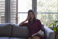 Woman talking on the phone at home - MOMF00334