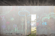 Concrete wall with colourful chalk drawings and open door - ZEF14866