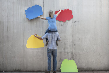 Woman sitting on a man's shoulders attaching colourful cloud shapes to concrete wall - ZEF14869