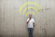 Man holding cell phone with yellow chalk wifi sign above his head - ZEF14872