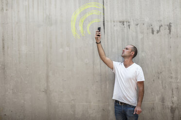 Man holding up phone looking for signal with wifi sign drawn in yellow chalk on concrete wall - ZEF14875