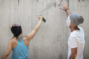 Man and woman wearing masks spray painting a concrete wall - ZEF14878