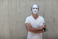 Man wearing a mask standing next to a concrete wall holding a can of spray paint - ZEF14881