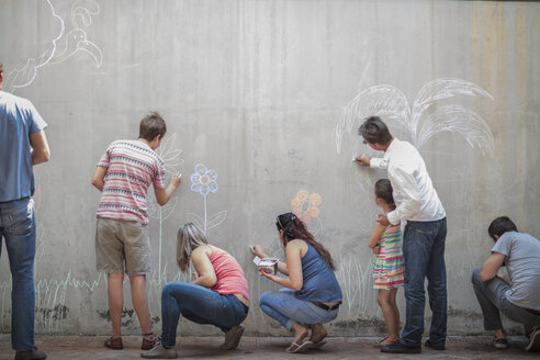People drawing colourful pictures with chalk on a concrete wall - ZEF14884