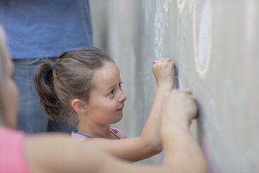 Girl drawing colourful pictures with chalk on a concrete wall - ZEF14887