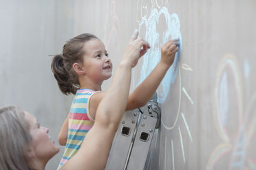 Mother and daughter drawing with chalk on a concrete wall - ZEF14890
