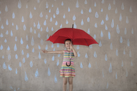 Girl holding a red umbrella standing next to a concrete wall with rain drop chalk drawings - ZEF14893