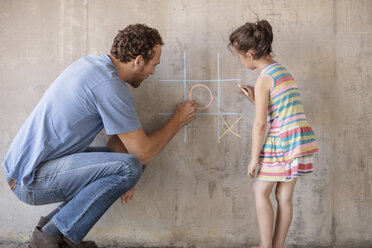 Father and daughter playing tic tac toe with chalk on a concrete wall - ZEF14896