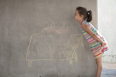 Girl pretending to blow out chalk birthday cake and candle drawing on concrete wall - ZEF14899