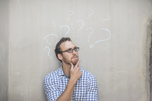 Man standing next to a concrete wall with chalk question mark drawings - ZEF14902