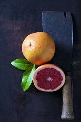 Whole and sliced Pink Grapefruit, leaves and an old cleaver - CSF28592