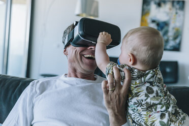 Happy man with baby wearing VR glasses - MFF04244