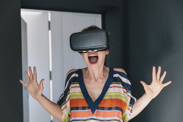 Amazed woman wearing VR glasses making a crazy face - MFF04247