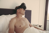 Tired man wearing VR glasses in bed - MFF04250