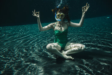 Woman with diving goggles and snorkel sitting in yoga pose underwater in a swimming pool - MFF04253