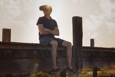 Mature man wearing VR glasses sitting on boardwalk during sunset and enjoying the view - MFF04262